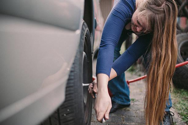 Jeune femme en train de changer ses pneus