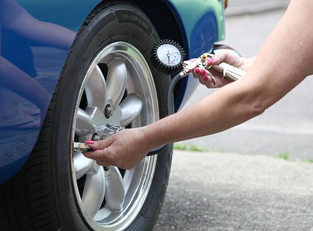 Femme qui mesure la pression de ses pneus pour les regonfler