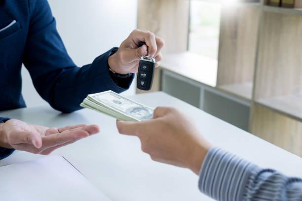 Acheteur qui conclue l'achat de sa voiture d'occasion avec un vendeur professionnel
