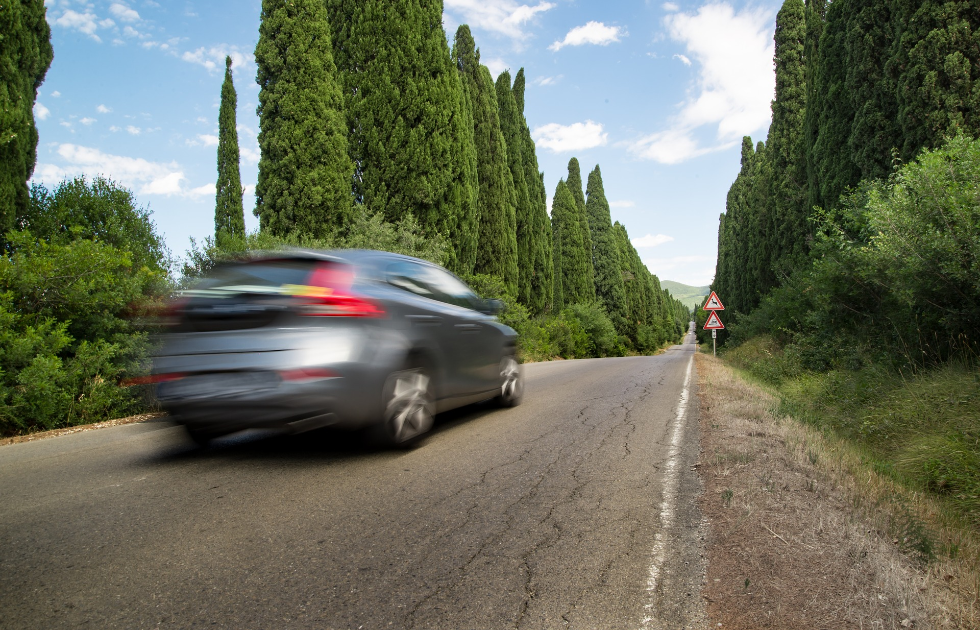 Voiture familiale en mouvement qui roule sur une route bordée de cyprès