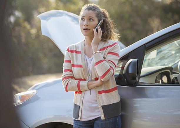 Jeune femme qui appelle une dépanneuse pour sa voiture d'occasion en panne