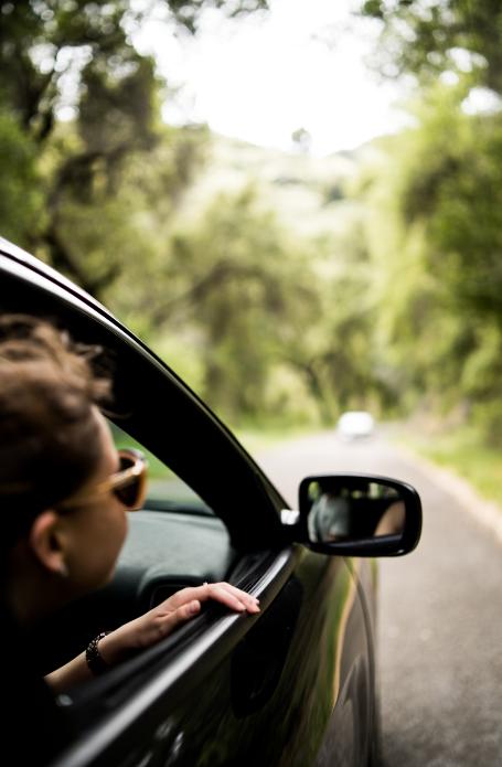 Jeune fille qui sort sa tête par la fenêtre d'une voiture